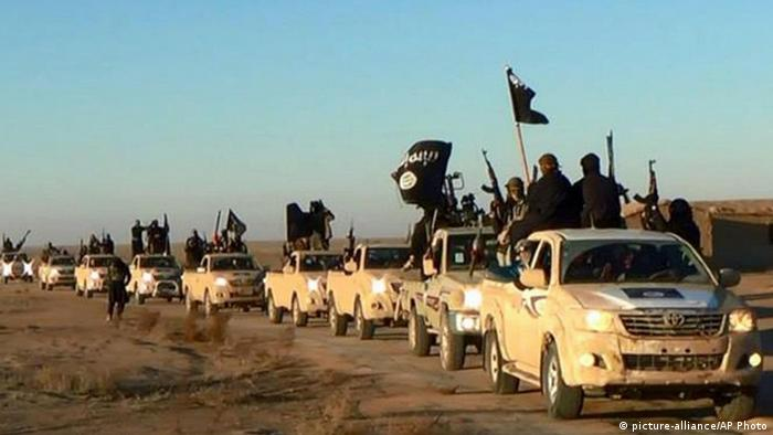 Militants of the 'Islamic State' group hold up their weapons and wave its flag on their vehicles in a convoy on a road leading to Iraq, while riding in Raqqa city in Syria