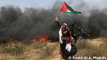 27.04.2018 *** A woman demonstrator holds a Palestinian flag during clashes with Israeli troops at a protest where Palestinians demand the right to return to their homeland, at the Israel-Gaza border in the southern Gaza Strip, April 27, 2018. REUTERS/Ibraheem Abu Mustafa