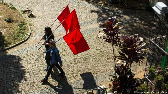 Duas pessoas carregam bandeiras vermelhas em São Paulo para a celebração do Dia do Trabalhador. A foto é de 1º de maio de 2015