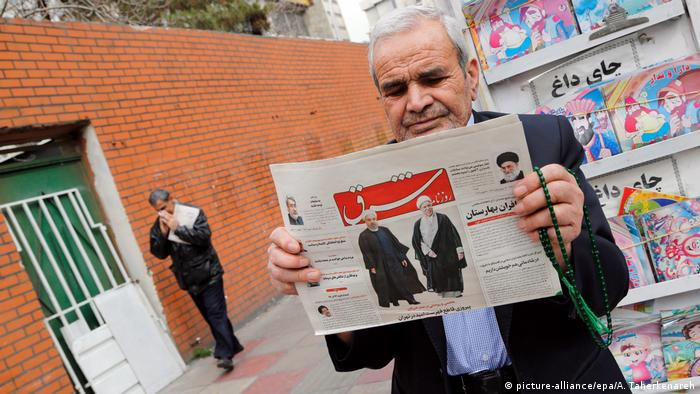An Iranian man holds a copy of the daily 'Shargh' newspaper