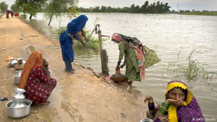 The image shows Pakistani women drawing water from a public tap