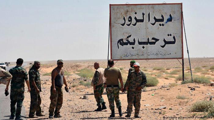 A file photo showing Syrian troops and pro-government gunmen standing next to a sign in Arabic which reads, Deir el-Zour welcomes you.