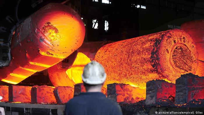 Red hot metal being moved across a heavy forge at a steel plant