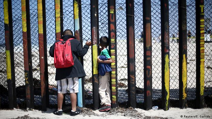 Two boys peer through a fence along the US-Mexican border