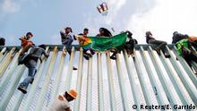 Members of a caravan of migrants from Central America sit on the border fence between Mexico and the U.S., as part of a demonstration prior to preparations for an asylum request in the U.S., in Tijuana, Mexico April 29, 2018. The banner reads Diversity without borders. REUTERS/Edgard Garrido
