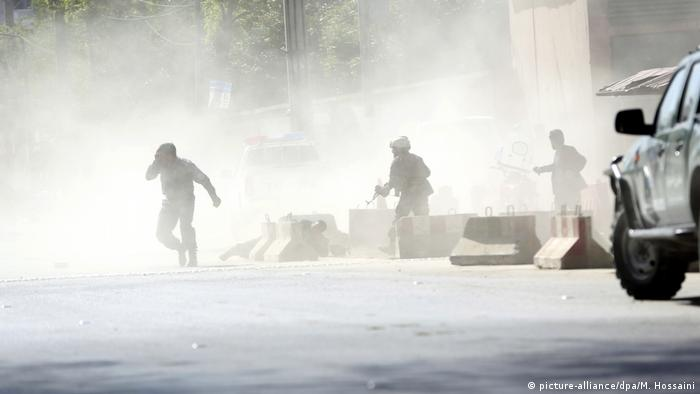 Afghani security forces walk through a cloud of smoke following an attack in Kabul (picture-alliance/dpa/M. Hossaini)