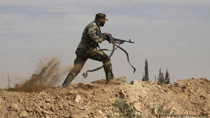 A sman running with a machine gun during fighting in Syria (picture-alliance/AP Photo/J.al-Helo)
