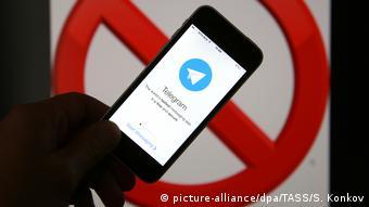 Смартфон, на экране которого открыто приложение Telegram, на фоне запрещающего знака