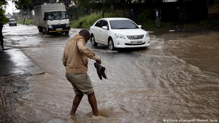 A man holds his shoes as he crosses a flooded street in downtown Nairobi