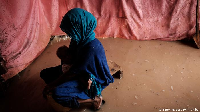A woman holds her child in a flooded shelter after a downpour at the Dadaab refugee complex in north-east Kenyar