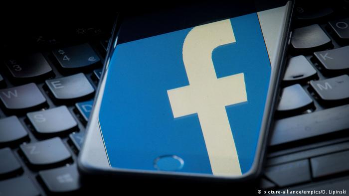 Отражение логотипа Facebook на экране смартфона