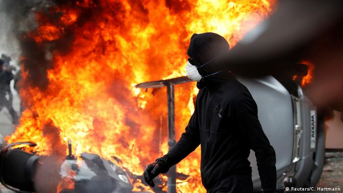 A masked and hooded protester walks past a burning car (Reuters/C. Hartmann)