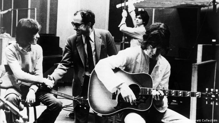 Regisseur Jean Luc Godard schüttelt Mick Jagger die Hand, daneben die Band Rolling Stones.