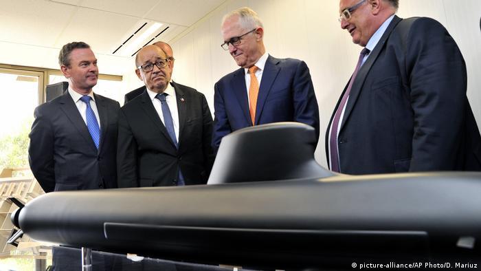 Der ehemalige australische Premierminister Malcolm Turnbull ((Zweiter von rechts) steht zusammen mit dem französischen Außenminister Jean-Yves Le Drian (Zweiter von links) vor einem Modell-U-Boot.