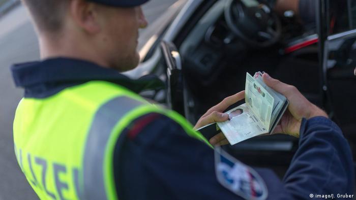 An Austrian border officer checks a passport