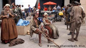 Actors in 18th century garb stand and sit