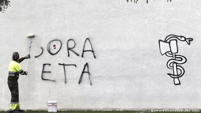 A cleaner removes the graffiti saying 'Long live ETA' from dowtown Pamplona