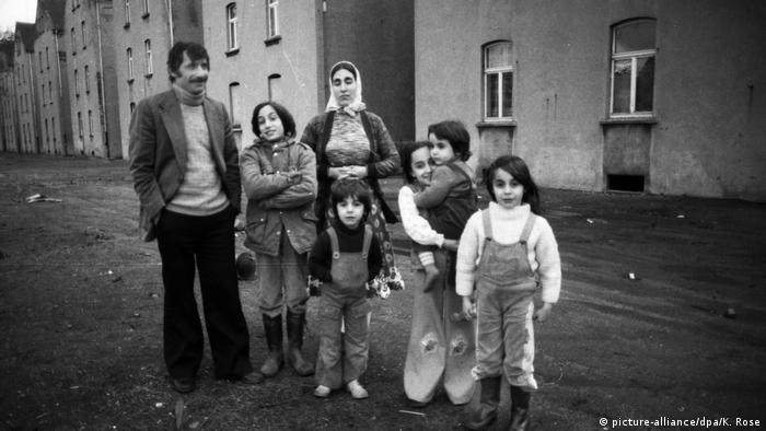 Turkish family in Germany in 1979 standing in front of a row of houses