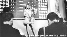 women standing on stage holding flowers and a medal in bare feet (1967) (picture-alliance/United Archives/TopFoto)