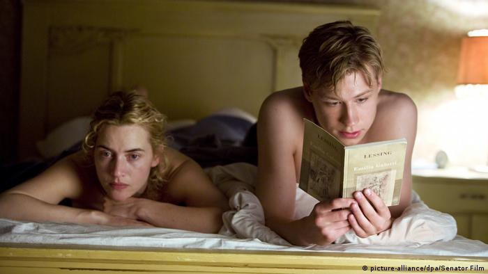 Film still The Reader, a young man lies on a bed and reads to a woman lying on her stomach next to him