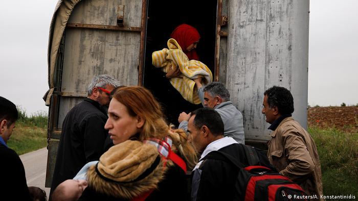 পুলিশের গাড়িতে প্রাথমিক রেজিস্ট্রেশন কেন্দ্রে যাচ্ছেন শরণার্থীরা