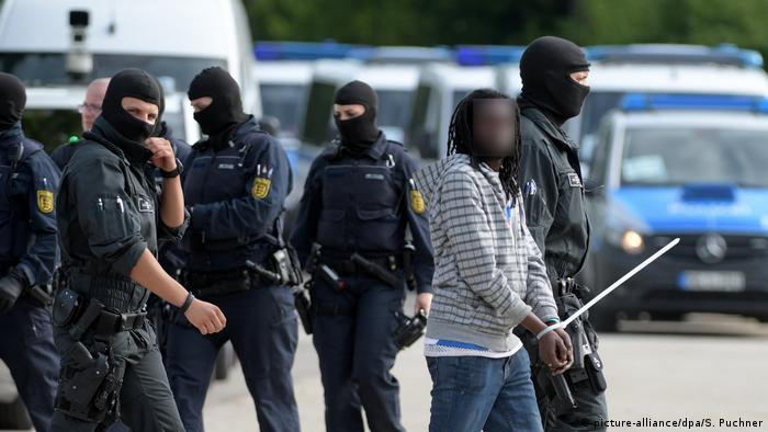 Police escort an asylum-seeker away