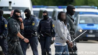 Полицейские уводят темнокожего беженца