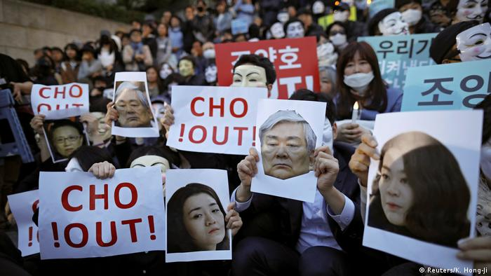 Protesters hold up placards reading 'Cho out!'