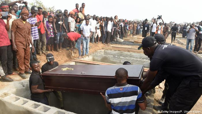 People watch as casket is lowered into grave