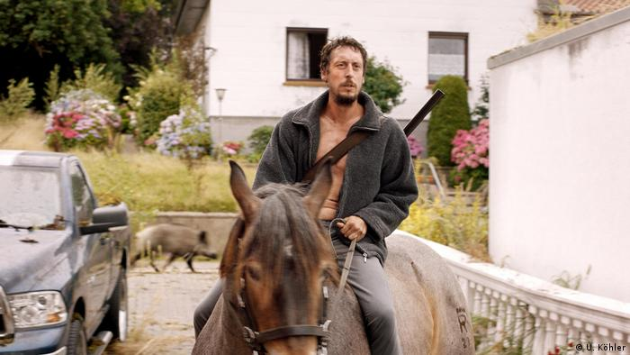 A man on a horse while a boar runs behind him from a film still 'In my Room' (U. Köhler)