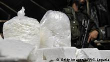 Colombian police personnel from an anti-narcotics unit custody part of some five tons of cocaine seized in an illegal laboratory producing cocaine hydrochloride belonging to the ERPAC (Ejercito Popular Antisubversivo de Colombia) criminal gang, on October 13, 2011, in the municipality of Puerto Gaitan, Meta department, Colombia. In the huge infrastructure, which had 34 rustic buildings capable of produce between 500 and 800 kilos of cocaine per week, police seized 5 tons of cocaine hydrochloride, a ton of cocaine base and 120 tons of precursor chemicals, according to authorities. AFP PHOTO/Guillermo LEGARIA (Photo credit should read GUILLERMO LEGARIA/AFP/Getty Images)