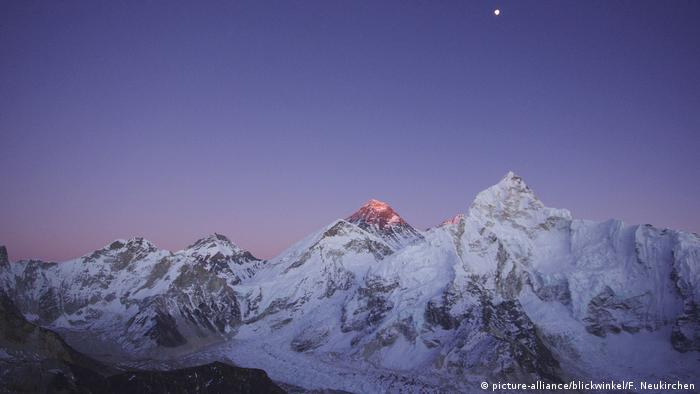 The moon rises above the Himalayan mountains