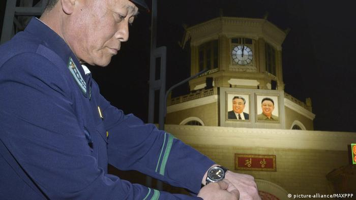 A man in uniform adjusts his watch