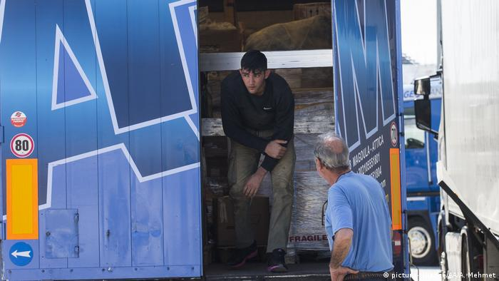 Ein Angehöriger der griechischen Küstenwache entdeckt in Patras einen Flüchtling in einem Lastwagen (Foto: picture-alliance/AA/A. Mehmet)