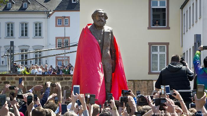 A red cover is pulled off the Karl Marx statue
