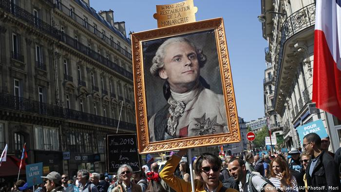 A protester holds up a poster of Macron as Kign Louis XIV (picture-alliance/AP Photo/F. Mori)