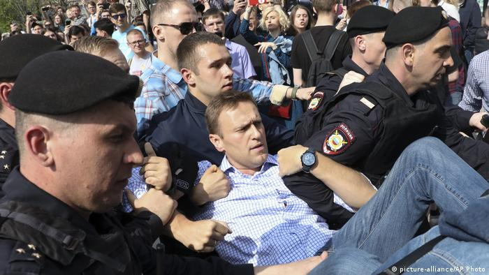 Opposition leader Alexei Navalny is carried away by police during an anti-Putin demonstration in Moscow.