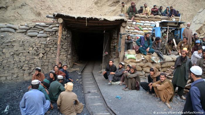 Miners wait outside the collapsed mine