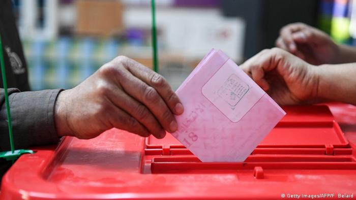 Mão de eleitor deposita voto na urna na Tunísia