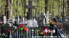 03.05.2018, Russland, Moskau: Eine Frau steht am Grab des deutschen Arztes Friedrich-Joseph Haass (die Schreibweise auf dem Grabstein weicht von der eingeführten deutschen Schreibweise ab) auf dem Wwedenskoje-Friedhof. (zu dpa Deutscher Armenarzt Haass in Moskau seliggesprochen am 06.05.2018) Foto: Emile Alain Ducke/dpa +++(c) dpa - Bildfunk+++   Verwendung weltweit