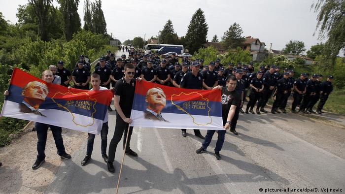 Dozens of police blocking road to prevent far-right supporters of a convicted war criminal from reaching an ethnically-mixed vilalge