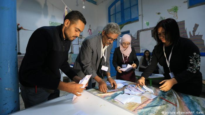 Women and men handle ballot papers at a polling station in Tunis (picture-alliance/AA)