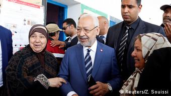 Ghannouchi in a blue suit posing at a Tunis polling statio