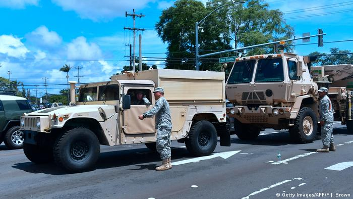 National Guard members stand next to their vehicles on a road in Hawaiii