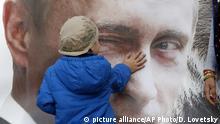 Kind streichelt Putin-Plakat