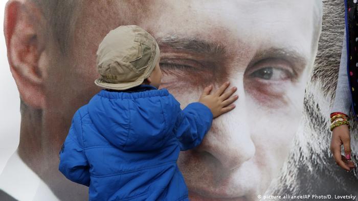 Дете докосва плакат с лика на Путин