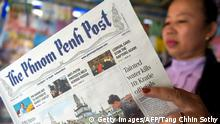 A woman reads the Phnom Penh Post (Getty Images/AFP/Tang Chhin Sothy)