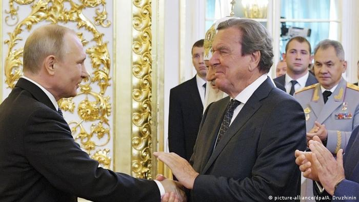 Former German Chancellor Gerhard Schröder shakes hands with Russian President Vladimir Putin at his inauguration