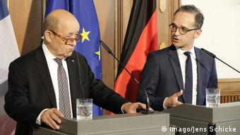 Maas and Le Drian stand together a podiums during a press conference (imago/Jens Schicke)