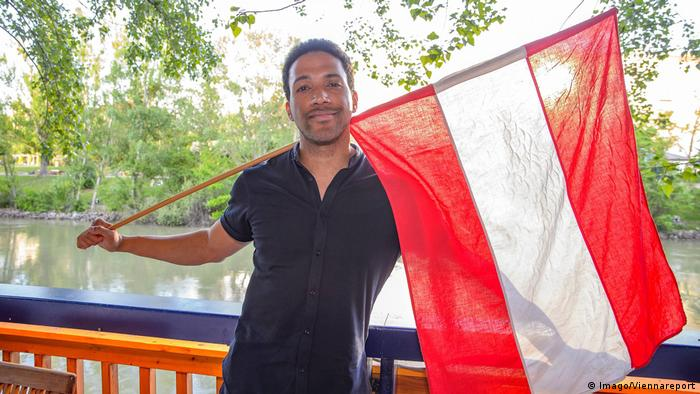 Cesar Sampson holds an Austrian flag (Imago/Viennareport)